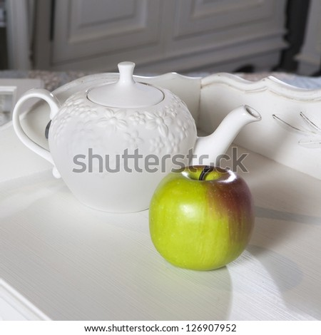 white  kettle standing with green apple  on wooden white table near wood wall. Copy space