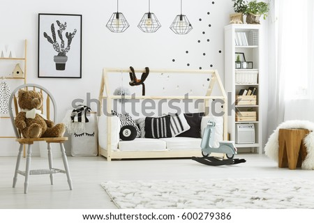 White kid bedroom with house bed, lamps, chair and poster #600279386