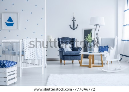 White kid's bed in bright room with armchairs, lamp and vase on table with marine decorations