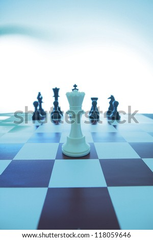 white king chess piece on chess board with black chess pieces at the back