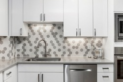 White kitchen built with shaker style cabinets and gray quartz countertop. Shows stainless steel appliances, white gray mosaic tile back splash. Polished Chrome faucet and hardware