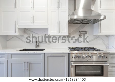 White kitchen built with shaker style cabinets and white quartz countertop. Shows stainless steel appliances, full granite backsplash. Polished Chrome faucet and hardware