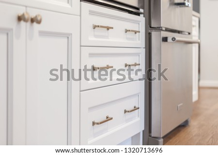 White kitchen built with shaker style cabinets. Shows cabinet details and brushed gold hardware knobs and pulls Сток-фото ©