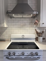 White Kitchen cupboard with white subway tile. Kitchen utensils are in a bowl ready for cooking with a small vintage copper colander hanging above the stove with a large kitchen hood exhaust.