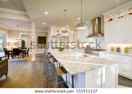 White kitchen design features large bar style kitchen island with granite countertop illuminated by modern pendant lights. Northwest, USA