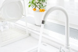White kitchen faucet running with blurred windowsill and dish dryer