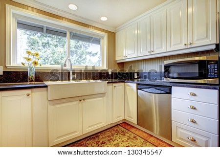 White kitchen interior with large sink and window. #130345547