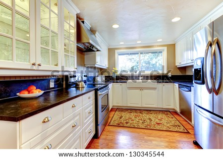White kitchen interior with large sink, window, hardwood floor.