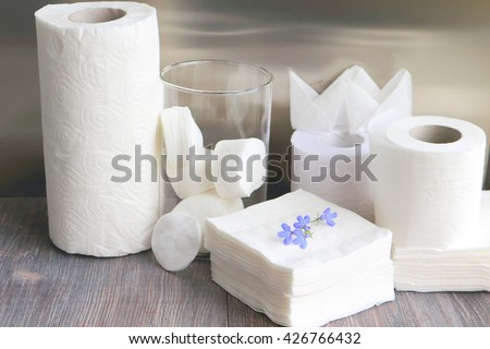 White kitchen towel, toilet paper, tissue and cotton pads  on a dark wooden table. #426766432
