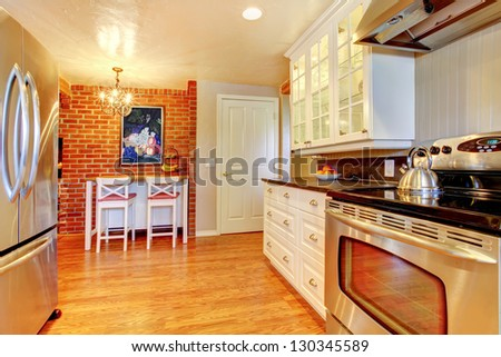 White kitchen with brick wall, hardwood and stainless steal stove and fridge.