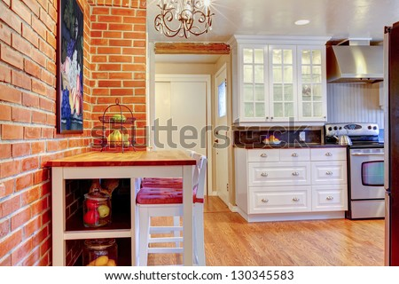 White kitchen with brick wall, hardwood and stainless steal stove with breakfast table.