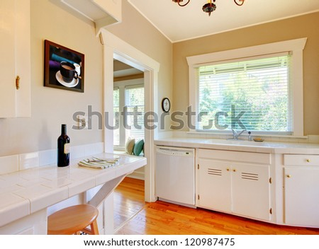 White kitchen with cherry hardwood floor, sink and window.