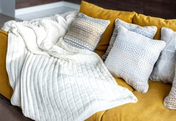 white knit blanket  on a yellow couch and nice decorative cushions