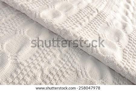 White knitted blanket folded diagonally