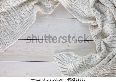 white knitted blanket. spit on the blanket. lying on white wooden floor in soft folds. in the centre of the empty place of inscription, text.