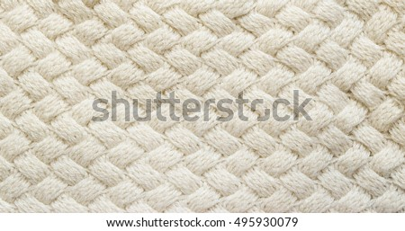 White knitted carpet closeup. Textile texture off white background. Detailed warm yarn background. Knit cashmere beige wool. Natural woolen fabric, sweater fragment.