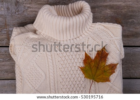 White knitted sweater with a maple leaf. Beautiful handmade knitted sweater on the old background.