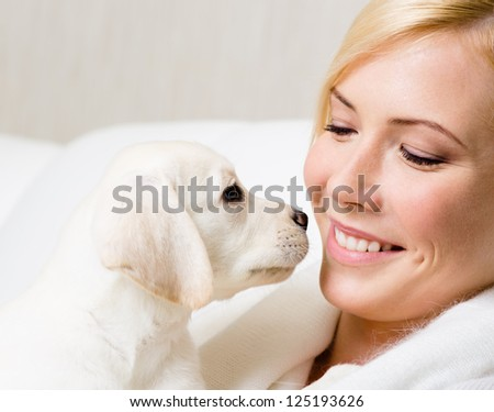 White Labrador puppy and woman sitting at the white leather sofa look at each other
