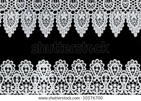 White lace forms a delicate border against black background.