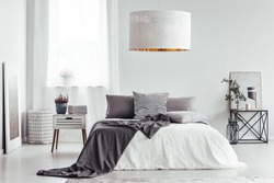White lamp in bright bedroom interior with heather and books on nightstand and patterned bedding on the bed