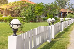 white lamp on fence with backyard garden blurred background