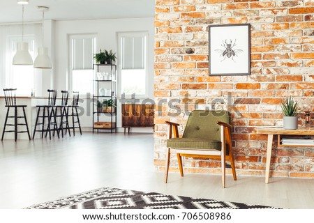 White lamps above countertop with bar stools in dining room with rustic furniture and poster on brick wall