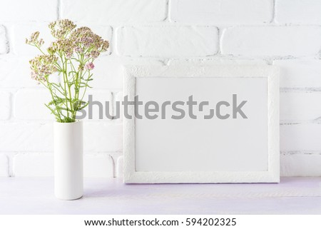 White landscape frame mockup with creamy pink flowers in cylinder vase near painted brick wall. Empty frame mock up for presentation design.  Template framing for modern art.