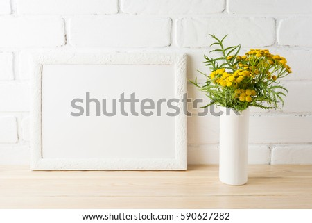 White landscape frame mockup with wild rich golden yellow flowers in vase near painted brick walls. Empty frame mock up for presentation design.  Template framing for modern art.