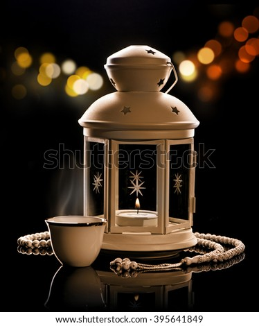 White lantern with Arabian coffee and rosary.\Ramadan mood at night with light decoration in the background.
