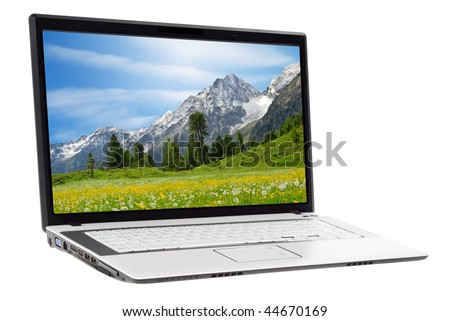 White laptop displaying a beautiful landscape of a meadow and mountains in spring