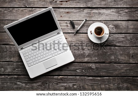 White laptop with coffee cup and pen on old wooden table.