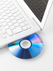 White laptop with violet-blue color dvd disk in slot-loading drive. Isolated on a white background.