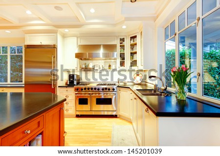 White large luxury kitchen with huge stove and refrigerator.
