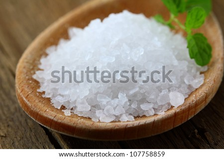 white  large sea salt in a wooden spoon