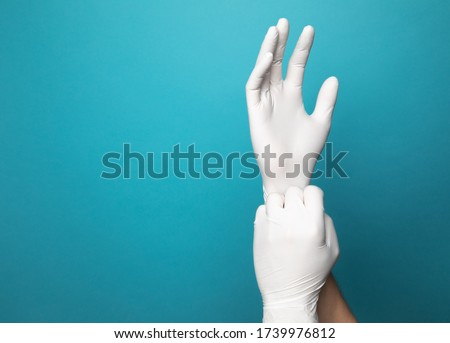 White latex gloves on two hands with a vibrant blue studio background. One gloved hand is pulling the end of the other glove down to simulate putting gloves on.