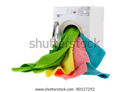 White laundromat with colorful landry in open door