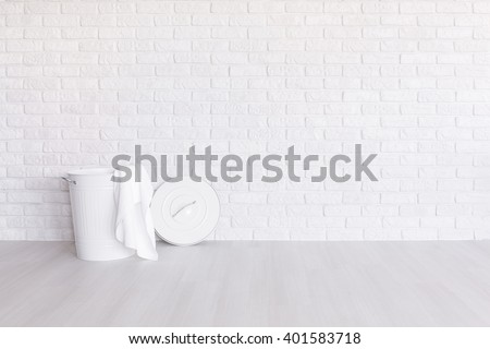 White laundry basket standing in spacious room with light flooring and brick wall #401583718