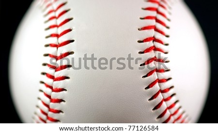 white leather baseball with red stitching on black background