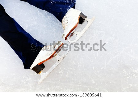 white leather skates on ice of outdoor open skating rink
