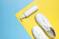 White leather sneakers, plastic bottles of cleaning products for shoes on blue yellow background flat lay top view. Natural leather shoe care, spray, foam, shoe deodorant, cosmetic shoe products