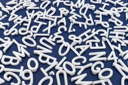 White letter and number are scattered chaotically on a table