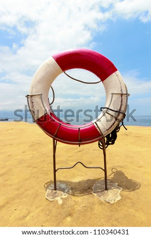 White life buoy with rope on the beach