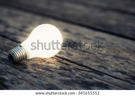 White light bulb glowing on the wood ground #341615552