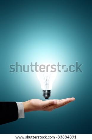 White light bulb on the hand businessmen on green background