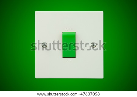 white light socket with a green switch on a green wall