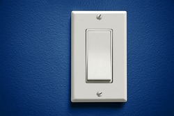 White light switch against blue wall