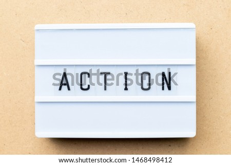 White lightbox with word action on wood background