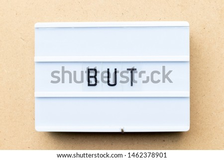 White lightbox with word but on wood background