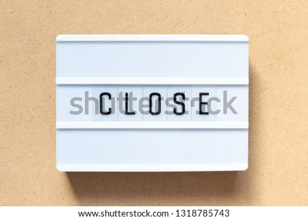 White lightbox with word close on wood background