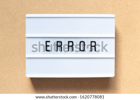 White lightbox with word error on wood background
